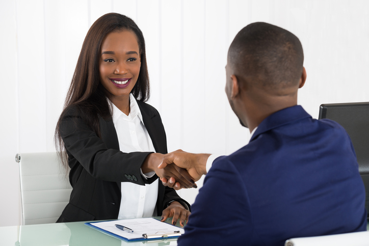 Two smartly dressed people shaking hands at an interview to demonstrate difficult interview questions