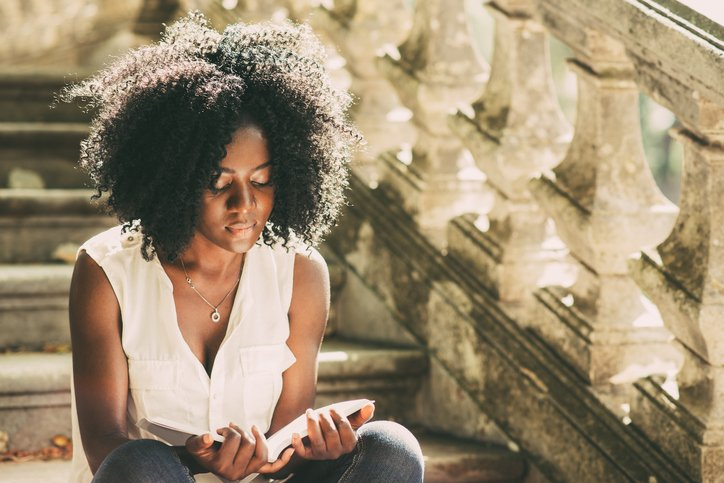 A young black woman reading books for aspiring medics