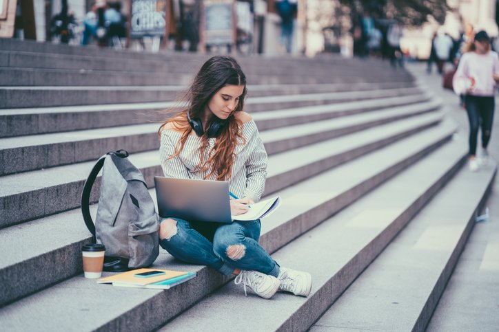 A girl sits on some concrete steps outside with her laptop and backpack surrounding her